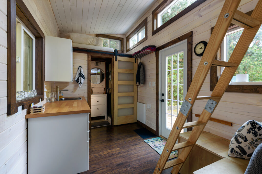 Tiny Living. Interior design of a dining room and kitchen in a tiny rustic log cabin.